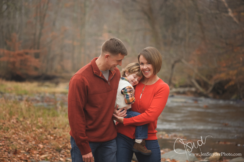 A family cuddles together by the Gunpowder River in Kingsville MD by Baltimore family photographer Jen Snyder