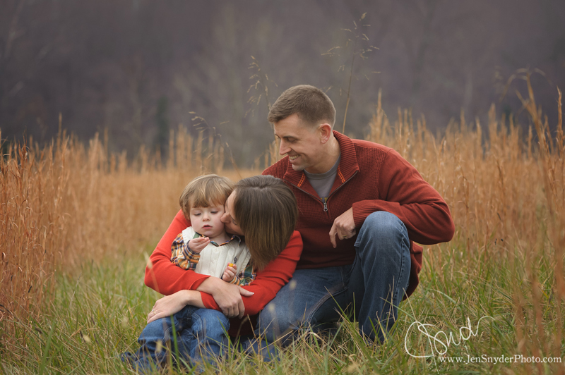 a family of 3 snuggle up together in a field by maryland portrait artist jen snyder
