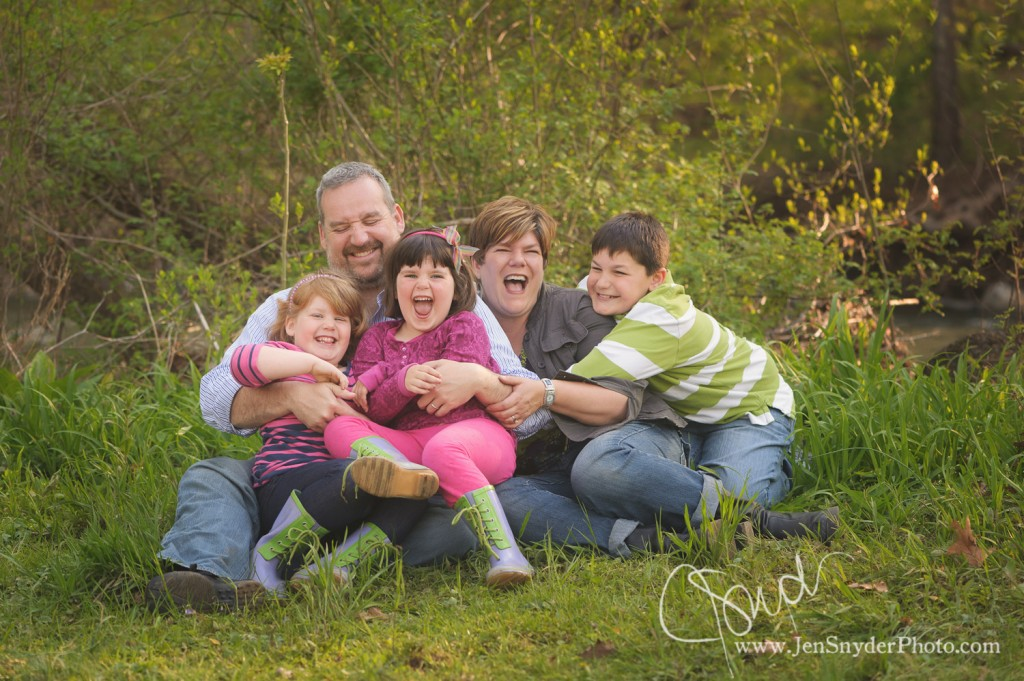 A Bel Air, MD family laughs together outside by harford county family photographer jen snyder