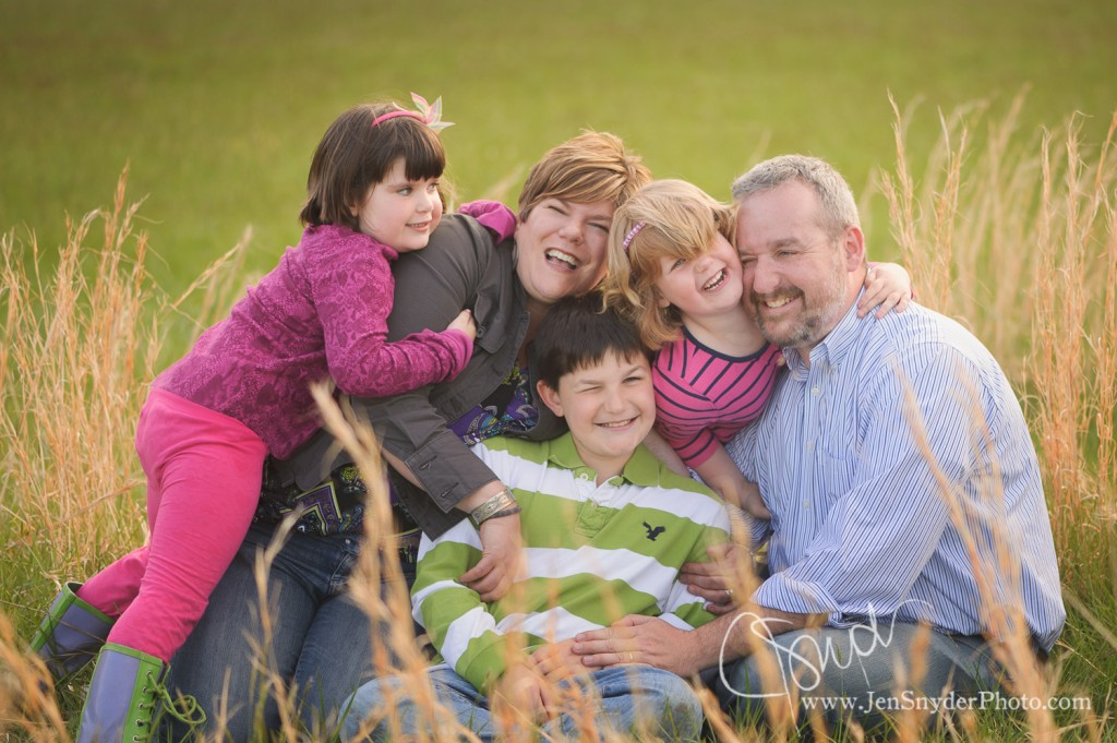 a family of five cuddles together in a field by harford county professional family photographer jen snyder in maryland