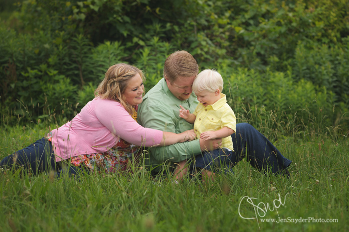 family-tickles-son-in-grass
