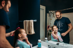 Little girl brushing her teeth, by maryland documentary photographer Jen Snyder https://jensnyderphoto.com