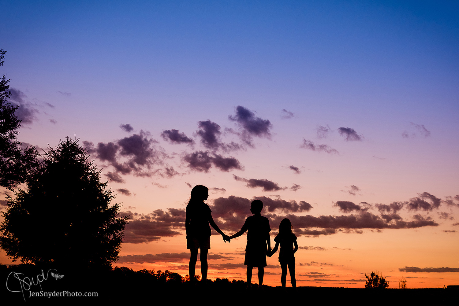 silhouette of 3 kids in the sunset, by jen snyder