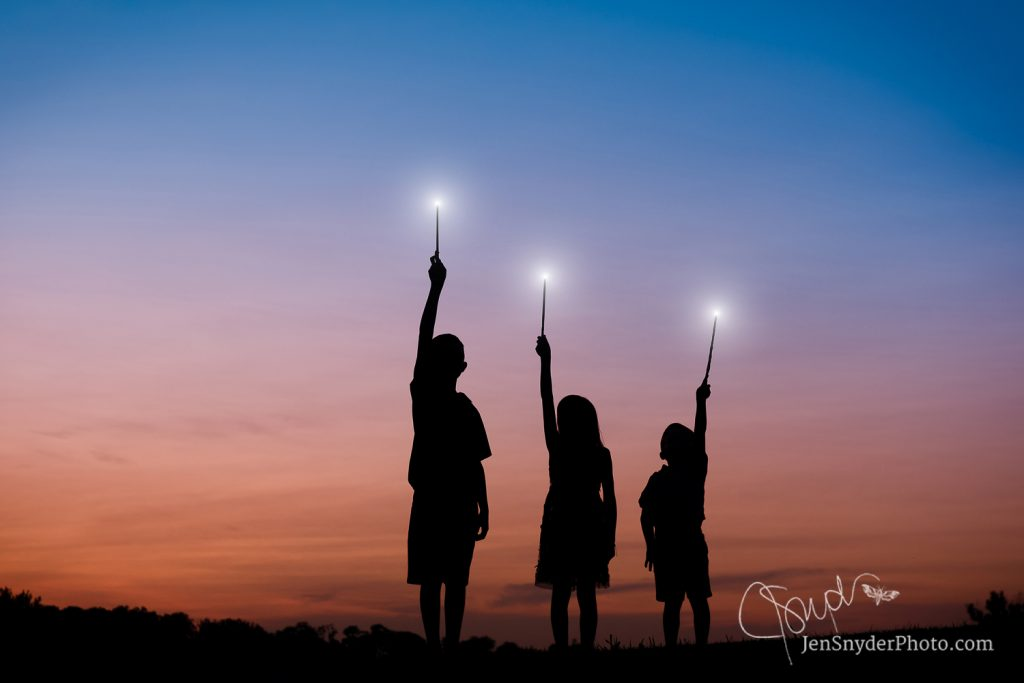 3 kids hold up magic glowing wands
