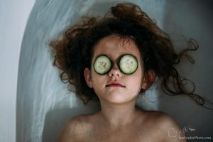 little girl in the tub with cucumbers on her eyes